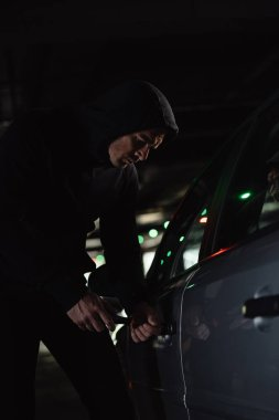 serious male robber in black hoodie intruding car by screwdriver
