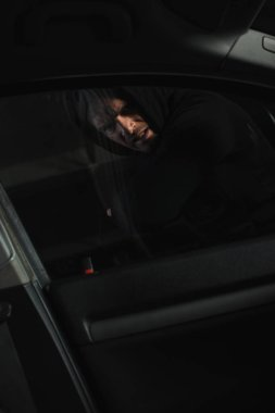 concentrated male robber breaking car window by elbow