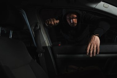 serious male thief in black hoodie stealing bag from car