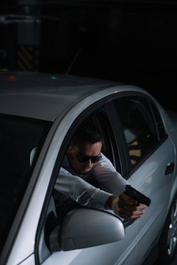 high angle view of male undercover agent in sunglasses aiming by gun from car
