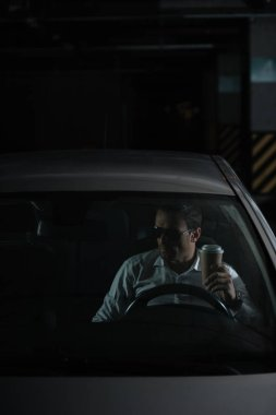 male undercover agent in sunglasses sitting in car with paper cup of coffee