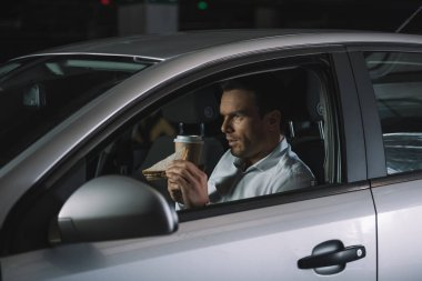 side view of male private detective drinking coffee and eating sandwich in his car