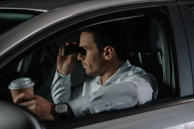 side view of undercover male agent doing surveillance by binoculars and drinking coffee in car