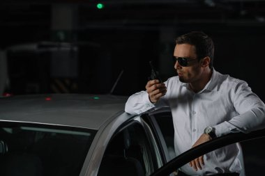 male undercover agent in sunglasses using talkie walkie near car