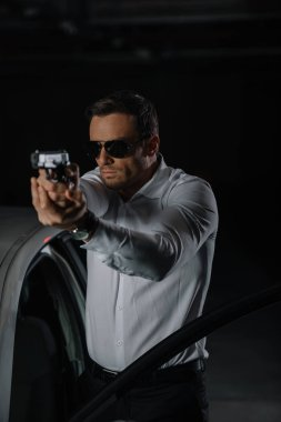 front view of undercover male agent in sunglasses aiming by gun