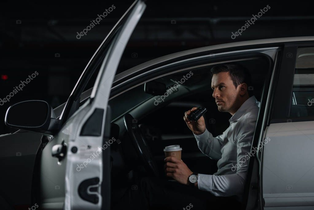 Undercover male agent with cup of coffee doing surveillance by binoculars from car