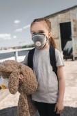 Kind in Schutzmaske halten Teddybär auf Brücke, Luft-Verschmutzung-Konzept