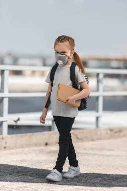 child in protective mask walking with book on bridge, air pollution concept