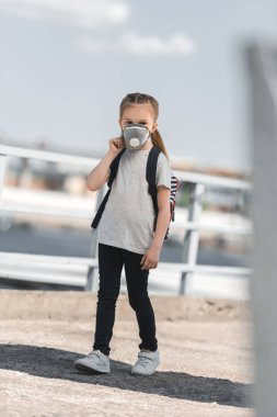 child in protective mask walking to school on bridge, air pollution concept