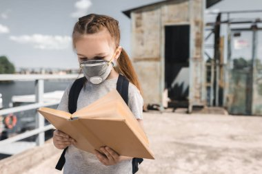 kid in protective mask reading book on bridge, air pollution concept