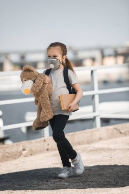 child in protective mask holding teddy bear and book on bridge, air pollution concept
