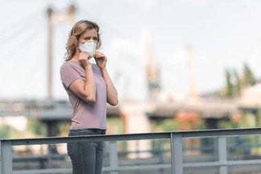 Köprüde koruyucu maske takıyor ve uzakta, hava kirliliği kavramı arayan kadın