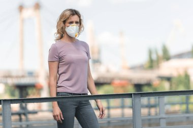 Köprüde duran ve uzakta, hava kirliliği kavramı seyir koruyucu maske kadında