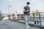 Fényképek Ázsiai tini a védő maszkot használ smartphone, levegő szennyezés fogalma