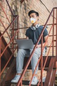 Fotografie asijské teen v ochranné masce sedí s notebookem na schodiště a koukal, koncept znečištění vzduchu