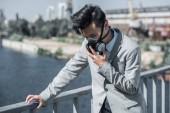 Fotografie Geschäftsmann in Schutzmaske Probleme mit atmen auf Brücke und stützte sich auf Geländer, Luft-Verschmutzung-Konzept