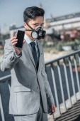 Photo asian businessman in gas mask showing smartphone on bridge, air pollution concept