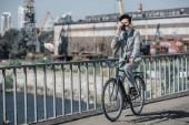 Fotografie asijský podnikatel v plynové masce jízda kole na mostě a mluví o smartphone, koncept znečištění vzduchu