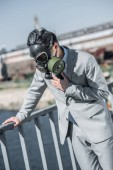 Photo businessman in gas mask having problem with breathing on bridge and leaning on railing, air pollution concept