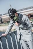 Fotografie podnikatel v plynových masek, potíže s dýcháním na mostě a opírali se o zábradlí, koncept znečištění vzduchu
