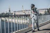 Fotografie podnikatel v plynové masce chůze po mostě, koncept znečištění vzduchu