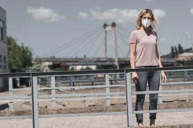 Köprü, hava kirliliği kavramı üzerinde koruyucu maske duran kadın
