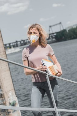 woman in protective mask standing on bridge with books, air pollution concept