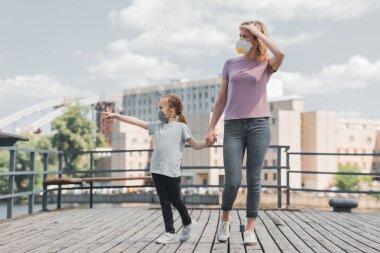 Anne ve kızı koruyucu maskeler iskelede, hava kirliliği kavramı elele