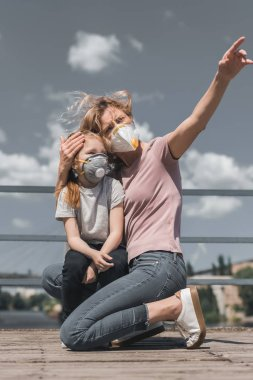 mother pointing on something to daughter in protective mask on bridge, air pollution concept