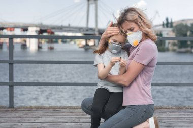 mother in protective mask hugging daughter on bridge, air pollution concept