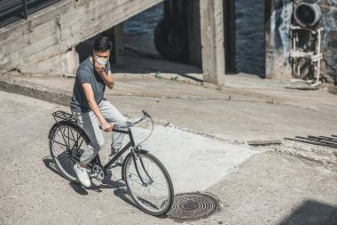 high angle view of asian teen in protective mask riding bicycle on bridge, air pollution concept