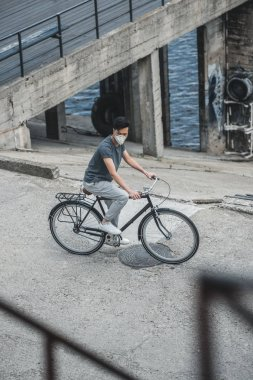 high angle view of asian teen in protective mask riding bicycle, air pollution concept