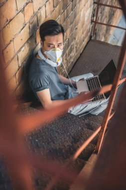 high angle view of asian teen in protective mask sitting with laptop on staircase, air pollution concept