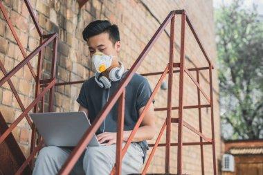 koruyucu maske merdiven, hava kirliliği kavramı laptop ile çalışma içinde Asya teen