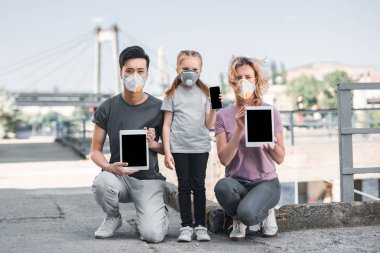 multicultural family with child in protective masks holding gadgets, air pollution concept