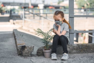 child in protective mask looking at green potted plant, air pollution concept
