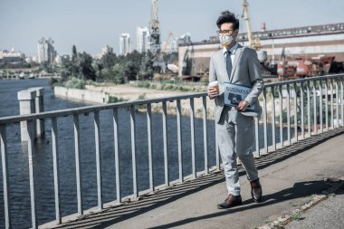 asian businessman in protective mask walking on bridge with coffee in paper cup, air pollution concept