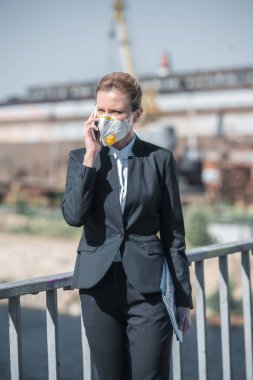 businesswoman in protective mask talking by smartphone at industrial district, air pollution concept