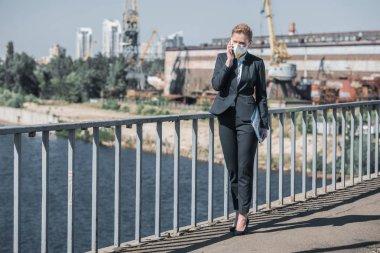 işkadını koruyucu maske smartphone tarafından köprüde, hava kirliliği kavramı konuşmak