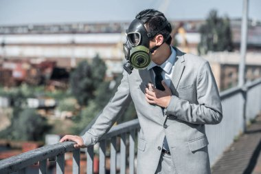 businessman in gas mask having problem with breathing on bridge, air pollution concept