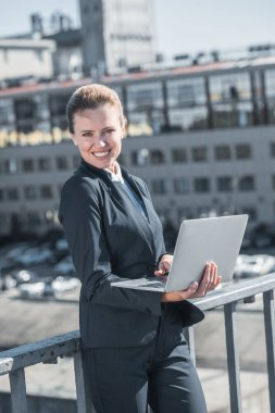 smiling attractive businesswoman standing with laptop on bridge and looking at camera