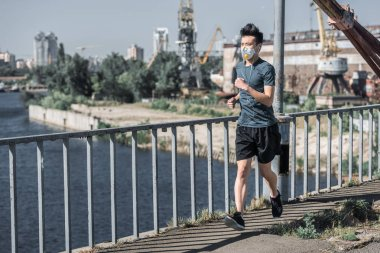asian teen running in protective mask on bridge, air pollution concept