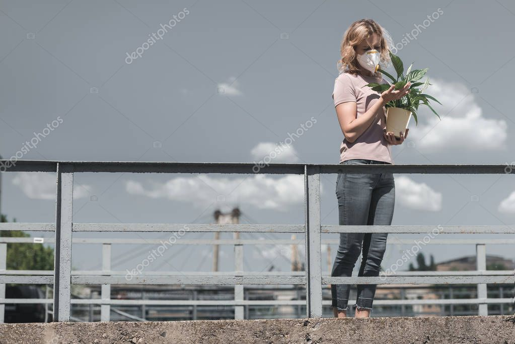 woman in protective mask looking at leaves of potted plant on bridge, air pollution concept