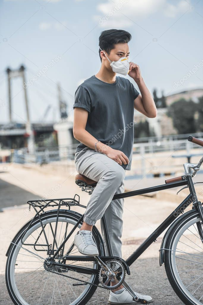 asian teen in protective mask standing with bicycle, air pollution concept