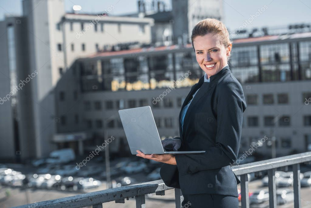 smiling attractive businesswoman standing with laptop on bridge