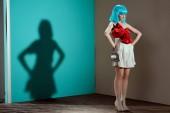 Fotografie po celé délce pohled krásné módní ženského modelu v modré paruce pózuje s rukou na pasu a hledat dál