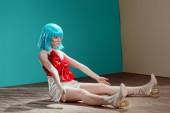 schöne Mädchen im blauen Perücke vorgibt, eine Puppe und sitzen auf dem Boden