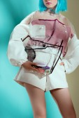 Fotografie cropped shot of fashionable girl in blue wig holding transparent cosmetic bag