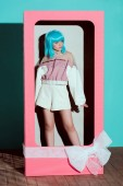 attractive girl in fashionable clothes and blue wig posing in decorative box with bow