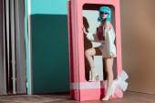 Fotografie Módní mladá žena v modrá paruka pózuje v Dekorativní růžový box s lukem